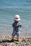 Baby boy on pebble beach Royalty Free Stock Image