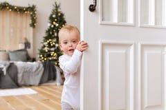 Children peeking out of the open room door. Baby boy peeking out of the open white room door royalty free stock photography