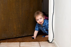 Baby Boy Peeks Through a Doorway While Playing with Cars Royalty Free Stock Photography