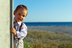 Baby boy picking out of wall, sea background Stock Photography