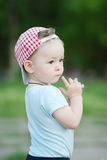 Baby boy in a plaid cap on a green background Stock Photography