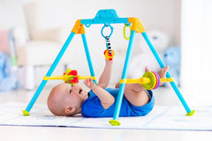 Baby boy on play mat. Child playing in gym. Cute baby boy on colorful playmat and gym, playing with hanging rattle toys. Kids activity and play center for early Stock Photos