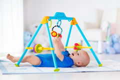 Baby boy on play mat. Child playing in gym. Royalty Free Stock Images
