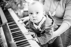 Baby boy near piano in Christmas fest stock images