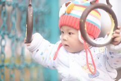 Baby boy  play the swinging rings Royalty Free Stock Images