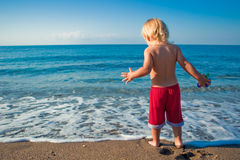Baby boy play with wave Stock Photos
