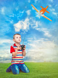 Baby boy playing with airplane on the control on the green lawn. Boy playing with airplane on the remote control stock photo