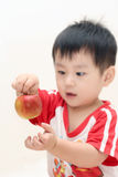 Baby boy playing an apple royalty free stock photo