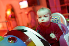 Baby boy playing arcade game machine. At an amusement park Royalty Free Stock Image