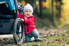 Baby boy playing in autumn forest with stroller, outdoors fun. Happy child on hiking trip in woods, looking at camera Stock Photos