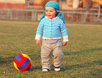 Baby boy playing ball in the football field. Stock Images