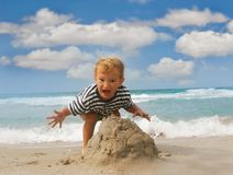 Baby boy playing on beach. Baby boy playing with sand on beach Stock Image