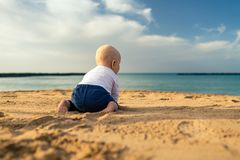 Baby boy playing on a beach stock image