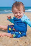 Baby Boy Playing at the Beach. Baby Boy Wearing Blue Shirt Playing in the Sand at the Beach Stock Photo