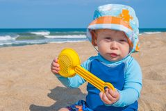 Baby Boy Playing at the Beach. Baby Boy Wearing Blue Shirt Playing with Toys in the Sand at the Beach Stock Image
