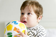 Baby boy. Playing on the bed with the ball Stock Image