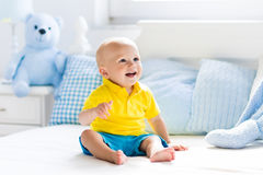 Baby boy playing on bed in sunny nursery Stock Image