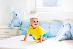 Baby boy playing on bed in sunny nursery Royalty Free Stock Photo