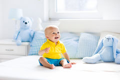 Baby boy playing on bed in sunny nursery Stock Photo