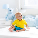 Baby boy playing on bed in sunny nursery Stock Images
