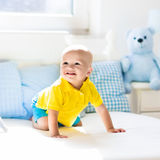 Baby boy playing on bed in sunny nursery Stock Photos