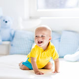 Baby boy playing on bed in sunny nursery Royalty Free Stock Images