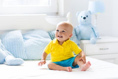 Baby boy playing on bed in sunny nursery Royalty Free Stock Photos