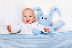 Baby boy playing with blue knitted bunny toy Stock Image