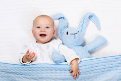 Baby boy playing with blue knitted bunny toy Stock Photography