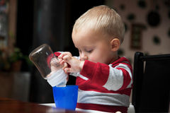 Baby boy playing with bottle and mug indoor Royalty Free Stock Images