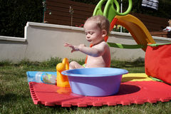A baby boy playing with water Royalty Free Stock Photography