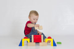 Baby boy playing with brightly coloured wooden blocks Stock Photos
