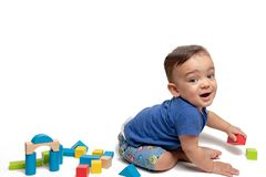 Baby boy playing with building blocks and truck in white background. 1yr old baby smiling and playing with building blocks in white background stock photo