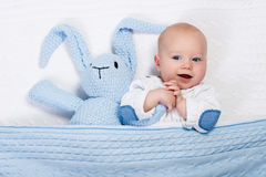 Baby boy playing with bunny toy in bed Royalty Free Stock Photos