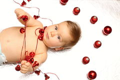 Baby boy playing with christmas bells and balls. Naked Baby boy upper body playing with christmas bells and balls Royalty Free Stock Image