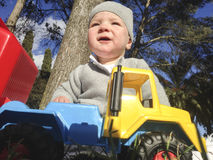 Baby boy playing with dump truck in the park. A sunny winter morning Stock Images