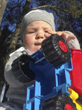 Baby boy playing with dump truck in the park. A sunny winter morning Royalty Free Stock Photography