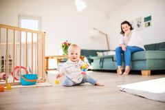 A baby boy playing on the floor at home, mother in the background. A baby boy playing on the floor at home. Unrecognizable mother sitting on the sofa in the royalty free stock photos