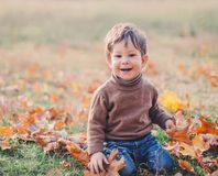 Baby boy playing with foliage in autumn park Stock Images