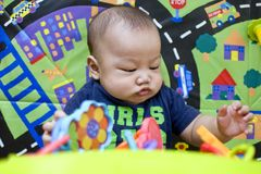 A baby boy is playing with hanging toys. While lying on a play mat Royalty Free Stock Photos