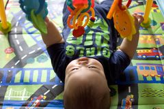A baby boy is playing with hanging toys. While lying on a play mat Royalty Free Stock Photo