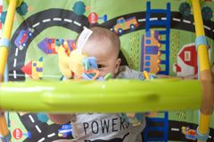 A baby boy is playing with hanging toys. While lying on a play mat Stock Image