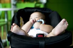 A baby boy is playing his rattle. While in the stroller Royalty Free Stock Photo