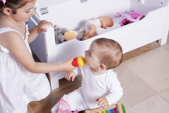 Baby boy playing with his sister at toys room Royalty Free Stock Photo