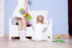 Baby boy playing with his sister at toys room Royalty Free Stock Photos