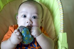 A baby boy is playing with hid toy stock photos