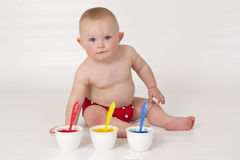 Baby boy playing with homemade fingerpaints. A baby boy in a reusable nappy makes a mess with paint Stock Images