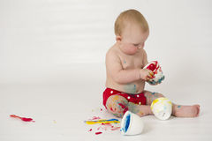 Baby boy playing with homemade fingerpaints. A baby boy in a reusable nappy makes a mess with paint Stock Image