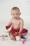 Baby boy playing with homemade fingerpaints. A baby boy in a reusable nappy makes a mess with paint Royalty Free Stock Photo
