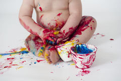 Baby boy playing with homemade fingerpaints. A baby boy in a reusable nappy makes a mess with paint Royalty Free Stock Photography